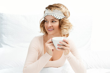 Woman drinking coffee on the bed at home
