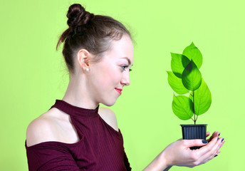 Girl holding in hand pot with small green plant.