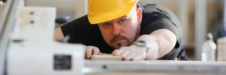 Worker using electric saw portrait