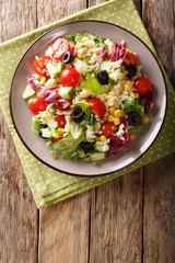 Italian vegetable salad with orozo pasta close-up on a plate. Vertical top view from above