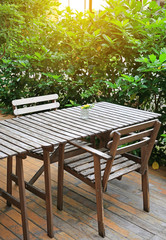 Wooden table and chair in the garden with glass of flower decoration.
