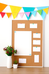 Colorful party flags hanging on cork board with blank note papers on wooden table background, birthday, anniversary, celebrate event, festival background