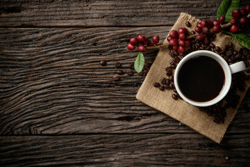 Top view mockup a cup of coffee with red ripe coffee beans.