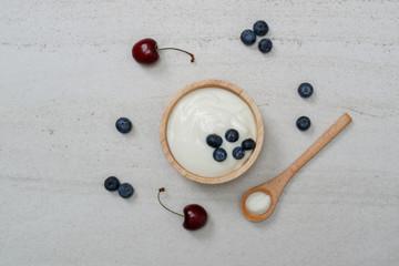 Fotobehang Zuivelproducten Yogurt in wooden bowl with fresh blueberries and cherry.Top view