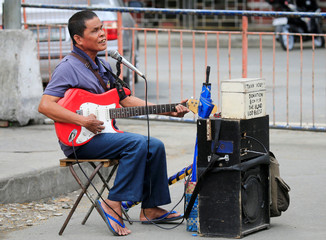 A blind man with an electronic guitar sings a song along the main street in Lawton, Metro Manila