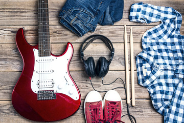 The accessories of a rock star: electric guitar, drumsticks, clothes and footwear on wooden background.