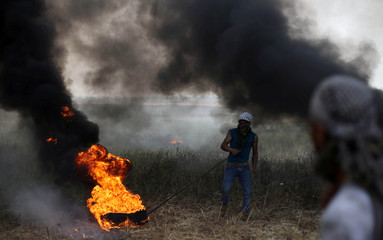 Palestinian protester moves a burning tire during clashes with Israeli troops at Israel-Gaza border, in the southern Gaza Strip