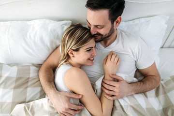 Portrait of young loving couple in bedroom