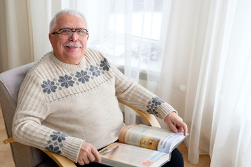 Senior man 75-75 years old sitting at home reading book in armchair