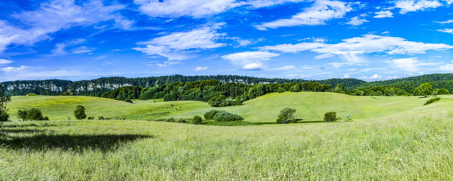 scenic landscape will hills and meadows in Le Frasnois in the Jura region in France