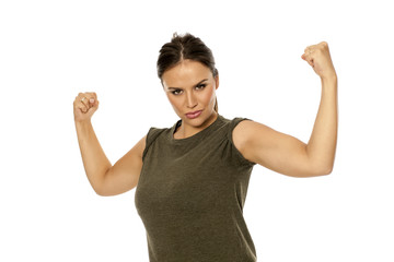 Young woman showing her arms on white background