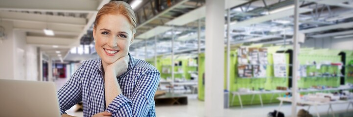 Composite image of smiling businesswoman sititng with laptop