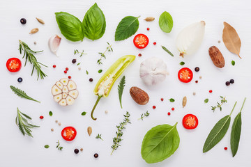 Various fresh herbs for cooking ingrediens peppermint , sweet basil ,rosemary,oregano, sage ,chilli bay leaves and lemon thyme on white wooden background with flat lay .