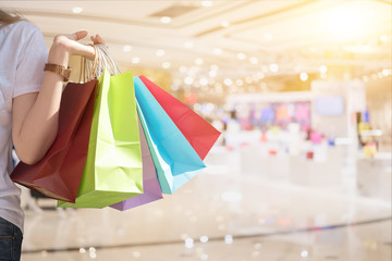 Attractive woman hand holding shopping bag in mall - Shopping Concept