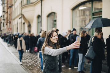 Smiling girl taking selfie through smart phone against crowd in city