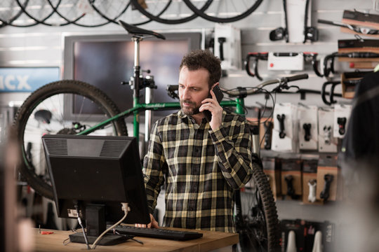 Small business owner on phone and computer in a store
