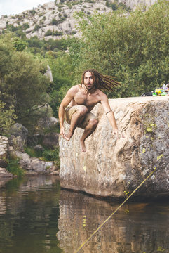 Mid aged man with drealocks practice slack line and jumps over the water in a lake in La Pedriza, Spain