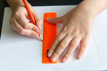 children's hands draw on a ruler