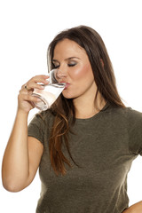 Young woman drink water from a glass on white background