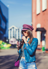 Fashionable woman in the street drinking morning coffee