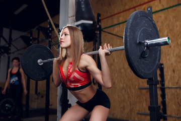 Image of sports woman squatting with bar