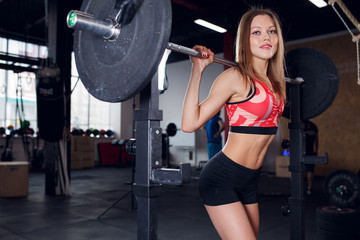 Image of young athletic woman squatting with barbell