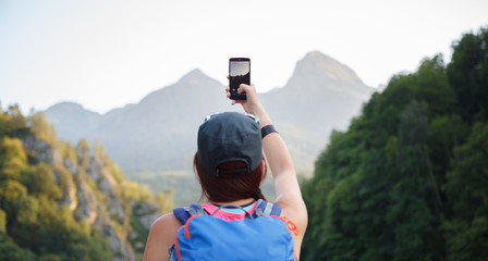 Picture from back of female tourist photographing mountain