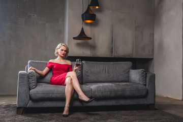 beautiful blonde woman in red dress sitting on sofa and drinking wine