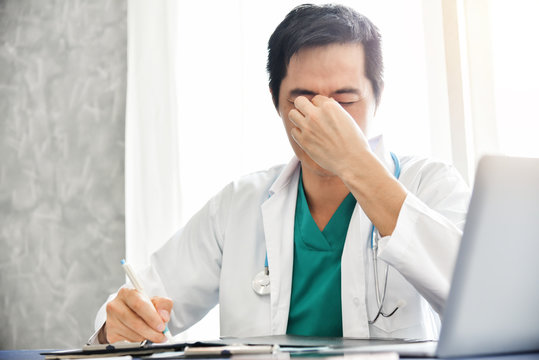 Stressed Young Asian male doctor is working.