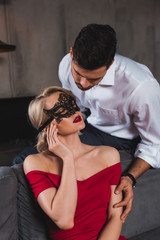 handsome man looking at beautiful sensual woman in red dress and black lace mask