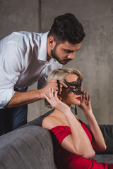 handsome man putting black lace mask on seductive woman in red dress