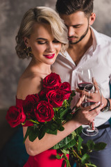 smiling young woman in red dress holding beautiful roses and drinking wine with handsome boyfriend
