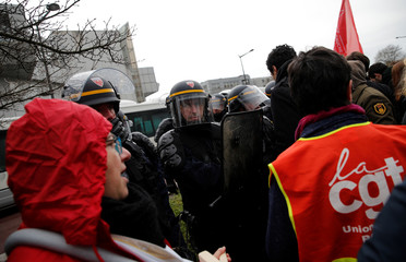 Workers face off with CRS riot police as they demonstrate outside the Rouen hospital ahead of French President Emmanuel Macron's visit to unveil an autism plan