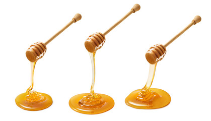 Set of wooden dippers with dripping honey isolated on white background