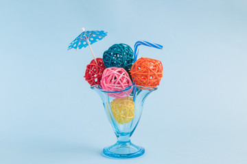 Rattan balls in form of ice cream scoops with paper parasol and drinking straw in glass cup on blue background minimalistic concept.