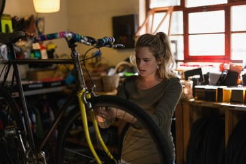 Female mechanic fixing bicycle in workshop