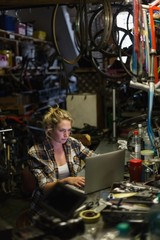 Female mechanic using laptop in workshop
