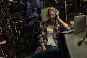 Female mechanic talking on mobile phone