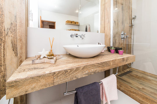 Modern interior of the bathroom. The washbasin is made of white massive shell on the table top made of marble in the color of wood. Minimalism and simplicity in a bright functional interior