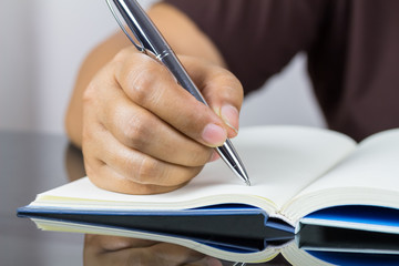 A man hand writing something on notebook