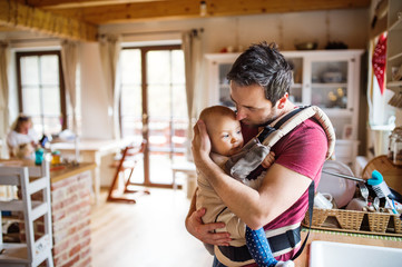 Father with a baby girl in a carrier at home.