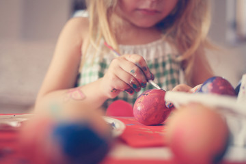 Toddler having fun painting Easter eggs.