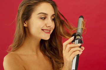 Young smiley woman making curly hair by ploy over red background