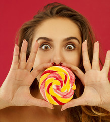 Portrait of a happy pretty girl holding sweet candy over red background