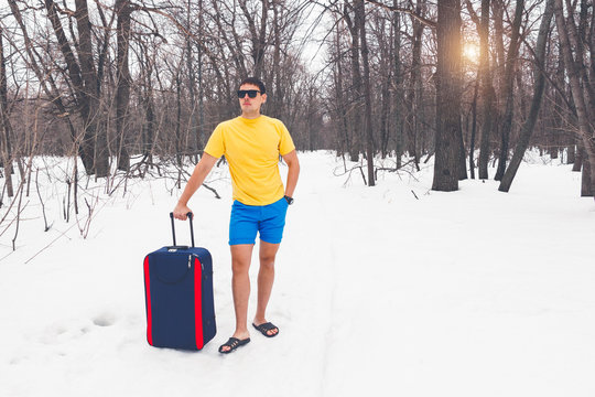 Travelling from winter to summer. Young cute guy in sunglasses, flip-flops, t-shirt and shorts with a tourist suitcase goes through the forest in the snow. Dream of vacation, sea, warm exotic country.