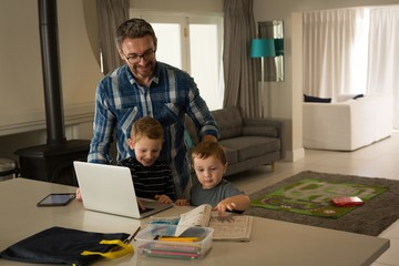 Father and his sons using laptop