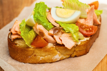 Salmon Sandwich Closeup. Salmon, eggs, lettuce and tomatoes on Bread