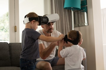 Father helping his son in using virtual reality headset in