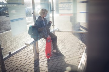 Woman using mobile phone at bus stop