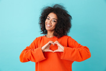Adorable american woman in colorful shirt looking on camera and gesturing heart shape with hands, isolated over blue background